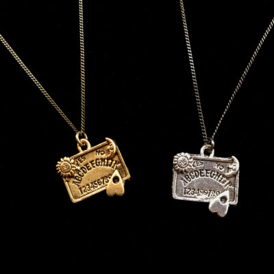 ouija board pendant sits on a dainty curb chain
